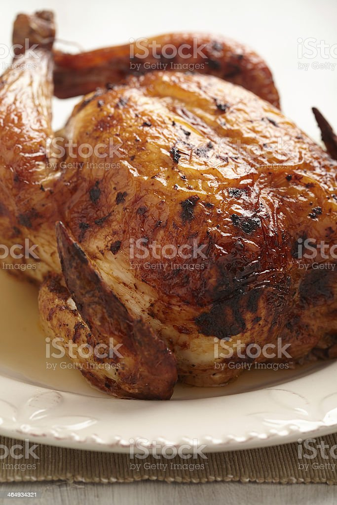 A perfectly roasted whole chicken on a white plate stock photo