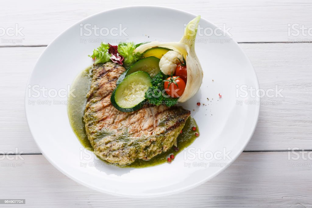 Perfectly seasoned grilled beefsteak served with vegetables and sauce royalty-free stock photo
