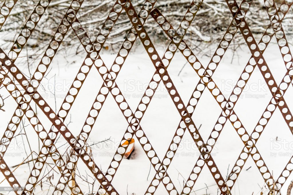 perforated fence on snow background. stock photo