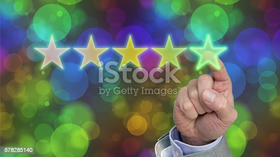 Hand of a businessman pressing the fifth green star of a performance evaluation rating on a colored bokeh background