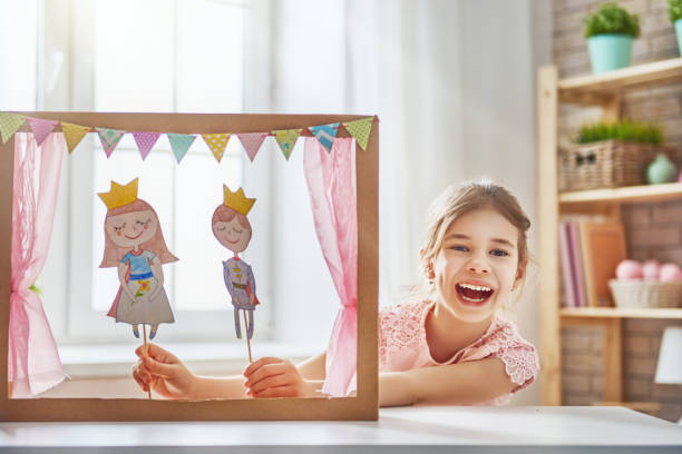 performance in the puppet theater Happy girl plays with performance in the puppet theater with prince and princess at home. Funny lovely child is having fun in kids room. puppet stock pictures, royalty-free photos & images