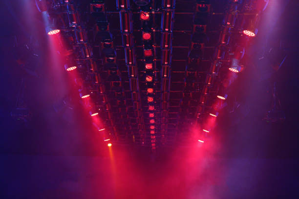 Performance moving lighting on construction light beam ray Performance moving lighting luminous rays on construction light beam ray downward in red color, on Concert and Fashion Show stage ramp ramp stock pictures, royalty-free photos & images