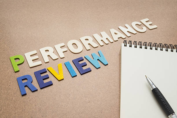 Performance review text with open spiral notebook and pen Performance review text with open spiral notebook and pen on brown background - concept of quality measurement annual event stock pictures, royalty-free photos & images