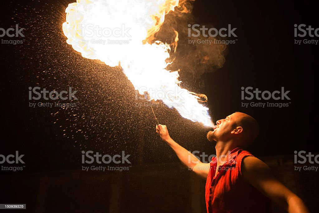 Performer breathing fire against a black background stock photo