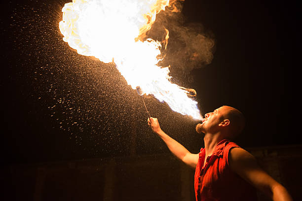performer breathing fire against a black background - circus stok fotoğraflar ve resimler