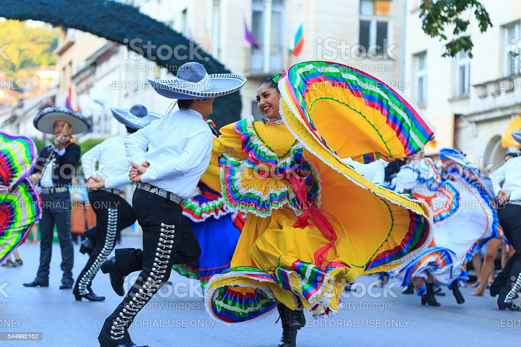 Performers from Mexican group in traditional costumes dancing on street stock photo