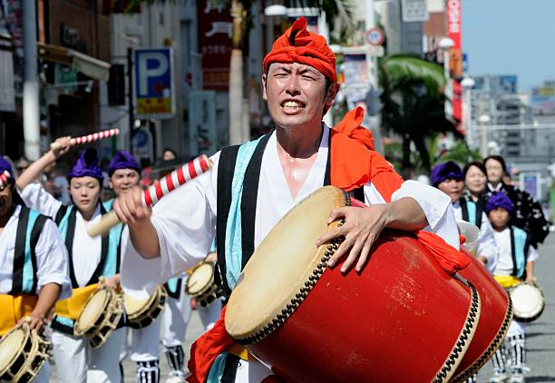 Performing... Despite the Heat Naha City, Japan - August 12, 2012: A taiko drummer squences his eyes as he walks down the street, performing in the brightness of the midday sun. despite stock pictures, royalty-free photos & images