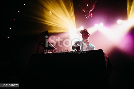 A young African American deejay performs for a crowd at a city night club. Colorful stage lights illuminate the stage behind him.