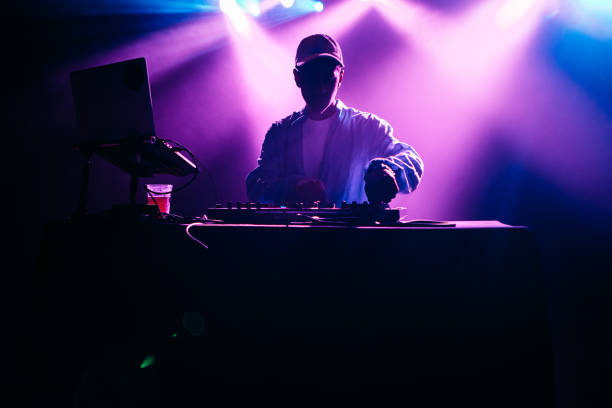 DJ Performing Music Set With Light Display A young African American deejay performs for a crowd at a city night club. Colorful stage lights illuminate the stage behind him. dj stock pictures, royalty-free photos & images