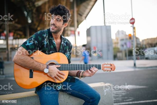 Charming young man, playing acoustic guitar on the street.