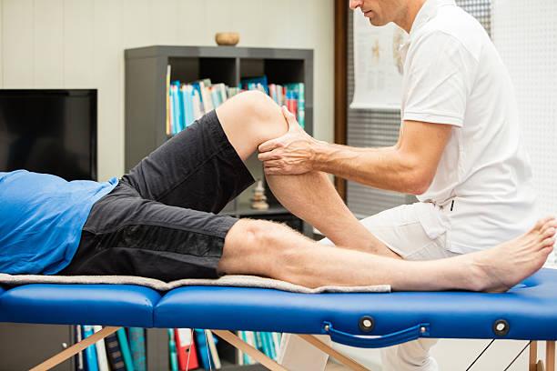 realiza el anterior cajón de prueba en la rodilla izquierda - masaje deportivo fotografías e imágenes de stock