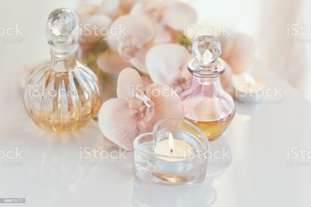 perfume and aromatic oils bottles surrounded by flowers and cand royalty-free stock photo