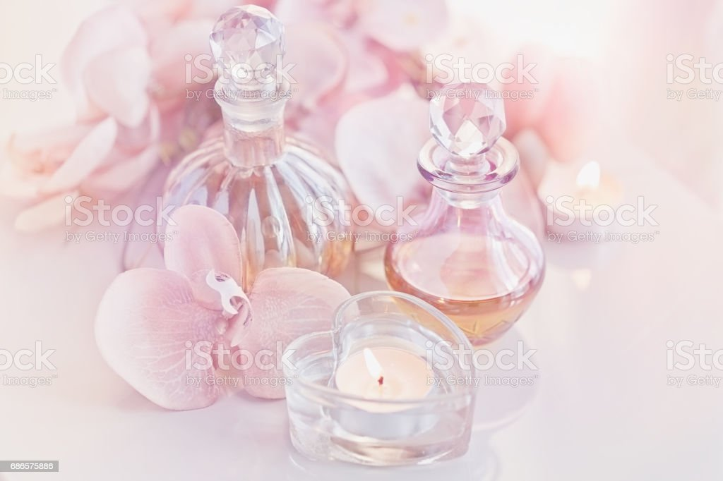 perfume and aromatic oils bottles surrounded by flowers and cand foto stock royalty-free