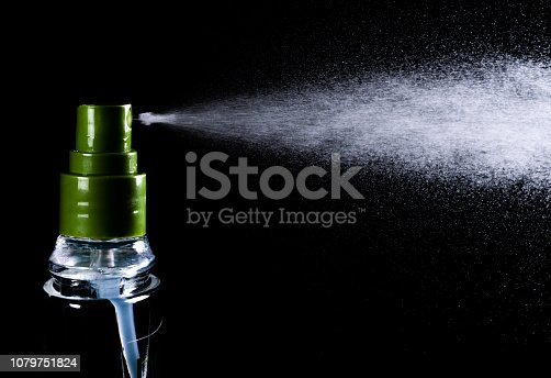 perfume bottle and perfume droplets on black background