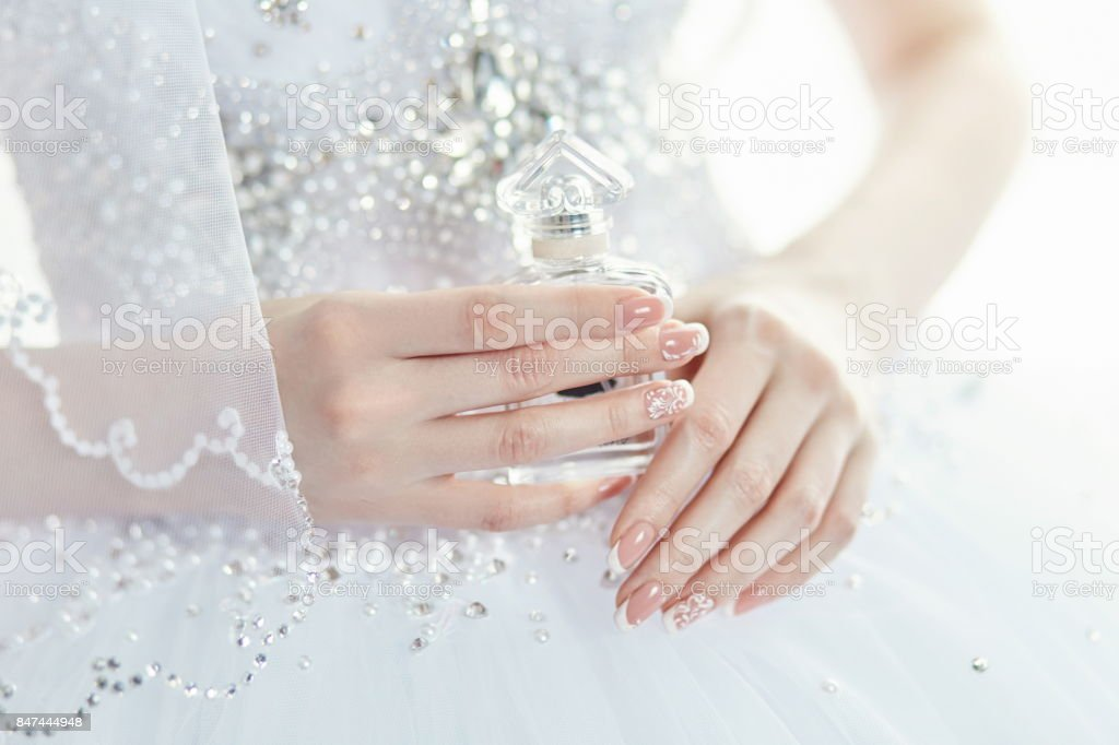 Perfume bottle in the hands of the bride. A woman is preparing for...