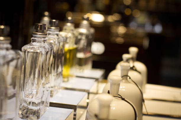 perfume bottles in store display shelf perspective view of white ceramic fragrance bells and perfume bottles in store shelf display with selective focus blotter stock pictures, royalty-free photos & images