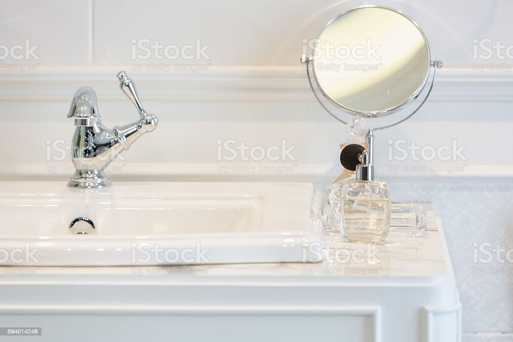 Perfume bottles on  white washbasin stock photo