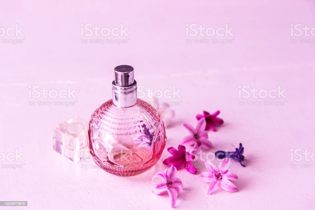 Perfume bottles with flowers. Pink background