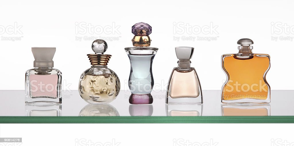 Perfume bottles with stoppers in a line on a glass shelf stock photo