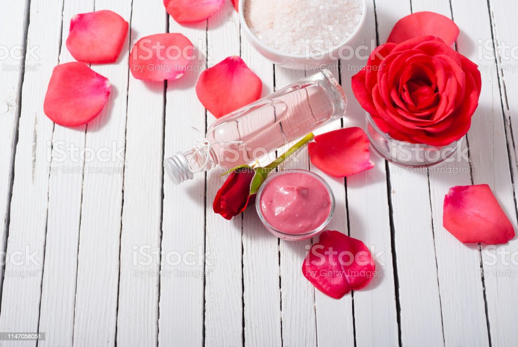 perfume, body care and beauty products with red roses, pink petals on...