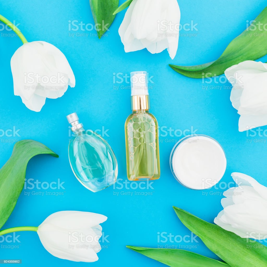 Perfume cream and tulips flowers on blue background beauty blog flat perfume cream and tulips flowers on blue background beauty blog flat lay izmirmasajfo