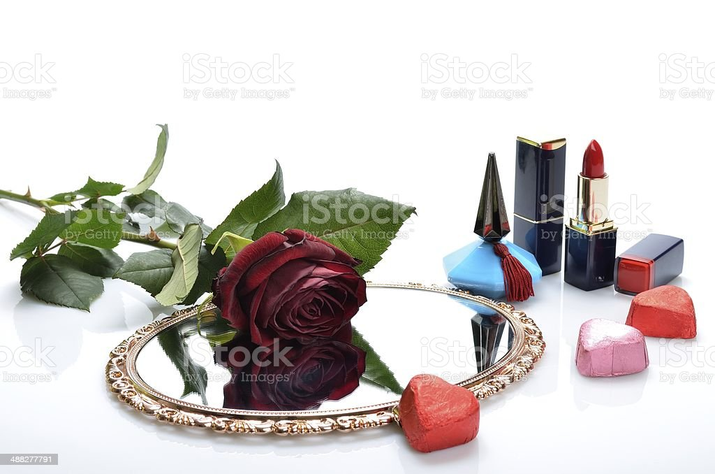 Perfume, lipstick, mirror candy hearts and a red rose royalty-free stock photo
