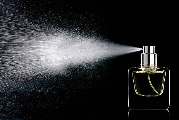 Perfume Spraying perfume bottle glass on a black background isolated spraying stock pictures, royalty-free photos & images