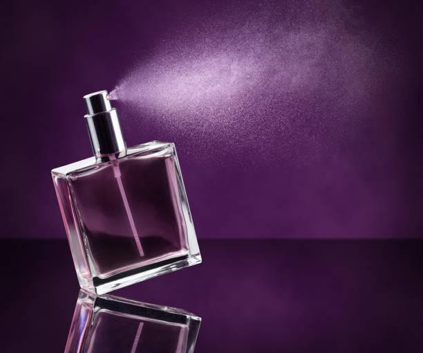 rozpylanie perfum na fioletowym tle - perfumowany zdjęcia i obrazy z banku zdjęć