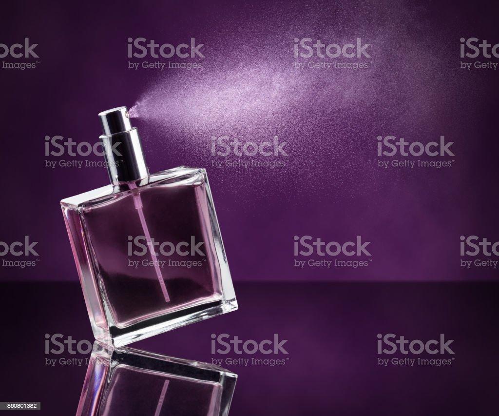perfume de rociadura sobre fondo púrpura - foto de stock