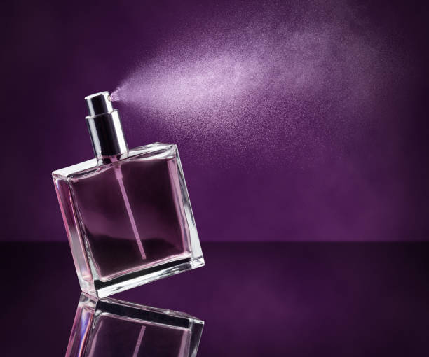 perfume spraying on purple background - profumi foto e immagini stock