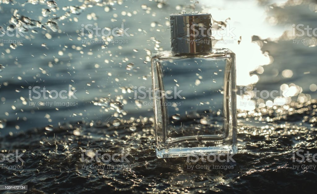 perfume with water drops at sea bacground stock photo
