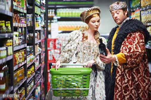 A king and queen selecting wine in the supermarket