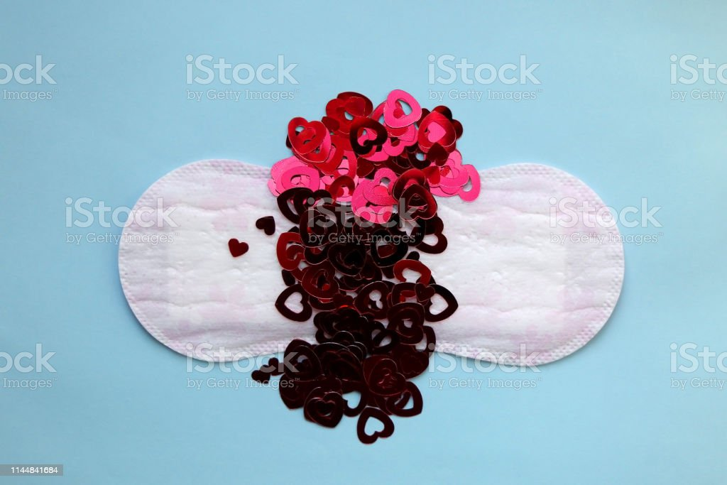 Period pad with red heart shaped sequins symbolizing menstruation....