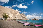 Tanning beds and umbrellas on Perissa beach, Santorini, Greece