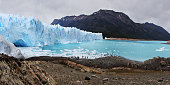 High-angle view of the impressive Perito Moreno glacier in the argentinian Patagônia. Turquoise icy waters and a group of tourists in the distance.