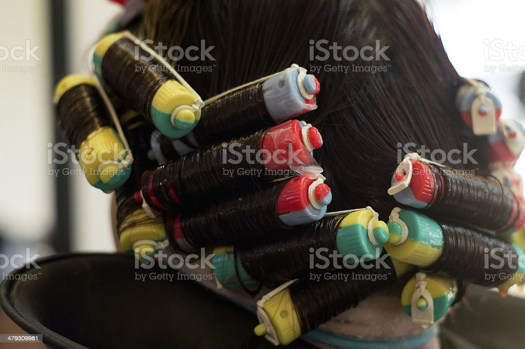 perm rolling the hair onto fine rollers or curlers stock photo