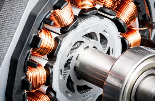 Detail of copper winding, stack and shaft of a  electric permeant magnet motor for home appliances. Selective focus and white background.