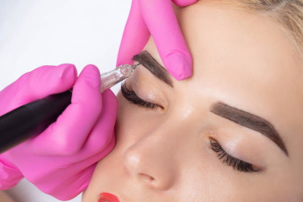 Permanent make-up for eyebrows of beautiful blonde woman in beauty salon. Closeup beautician doing eyebrows tattooing. stock photo