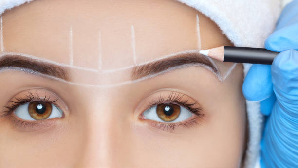 Permanent make-up for eyebrows of beautiful woman with thick brows in beauty salon. Closeup beautician doing  tattooing eyebrow. Face close-up. Make-up and Cosmetology concept. stock photo