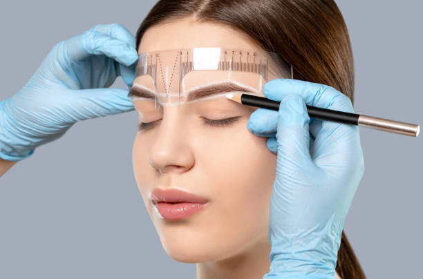 Permanent make-up for eyebrows of beautiful woman with thick brows in beauty salon. Closeup beautician doing tattooing eyebrow. Professional makeup and cosmetology skin care. stock photo