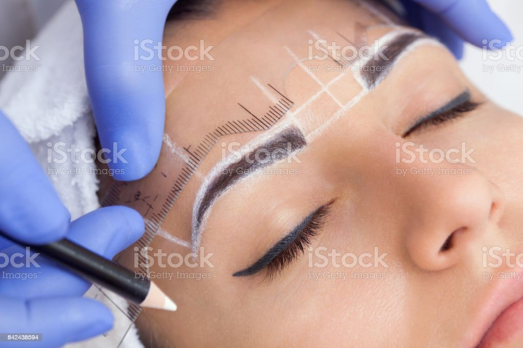 Permanent make-up for eyebrows of beautiful woman with thick brows in beauty salon. stock photo