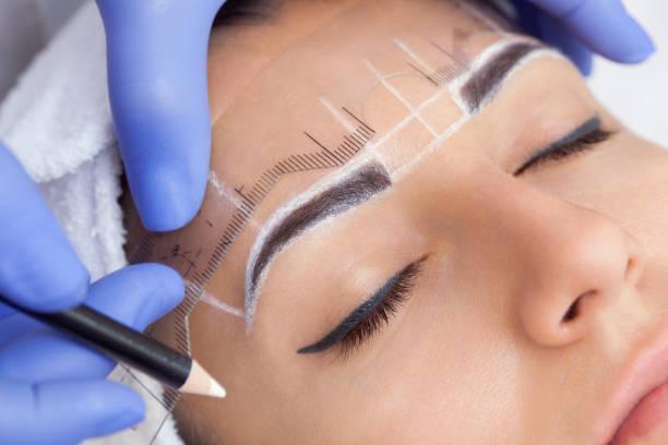 Maquillage permanent pour les sourcils de belle femme avec des sourcils épais dans un salon de beauté. - Photo