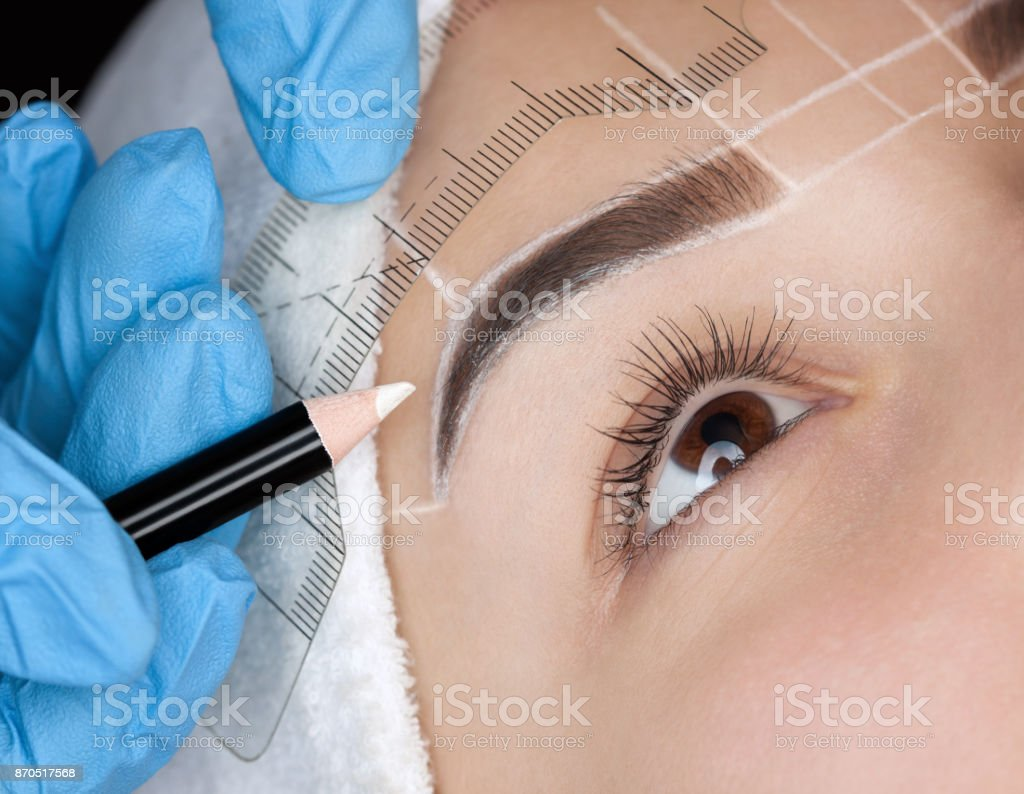 Permanent make-up for eyebrows of beautiful woman with thick brows in beauty salon stock photo