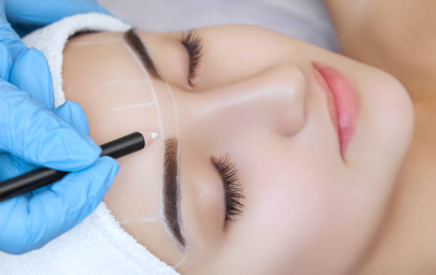 Permanent make-up for eyebrows of beautiful woman with thick brows in beauty salon. Permanent make-up for eyebrows of beautiful woman with thick brows in beauty salon. Closeup beautician doing  tattooing eyebrow. saloon stock pictures, royalty-free photos & images