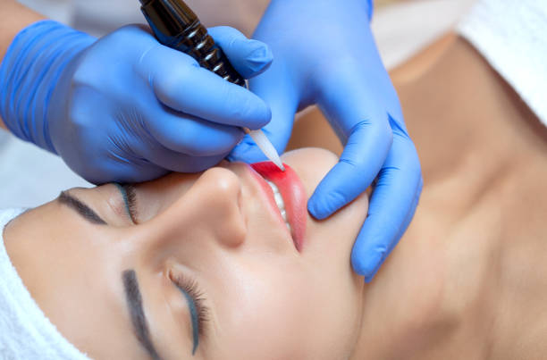 Permanent make-up for lips of beautiful woman in beauty salon. Closeup beautician doing lip tattooing. Face close-up. Make-up and Cosmetology concept. stock photo