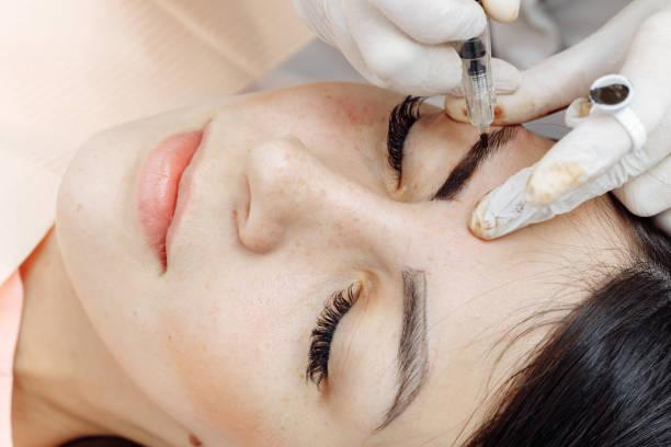permanent makeup, tattooing of eyebrows. cosmetologist applying make up - durabilidade imagens e fotografias de stock
