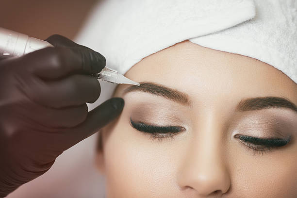 Permanent makeup. Tattooing of eyebrows Permanent makeup. Permanent tattooing of eyebrows. Cosmetologist applying permanent make up on eyebrows- eyebrow tattoo always stock pictures, royalty-free photos & images