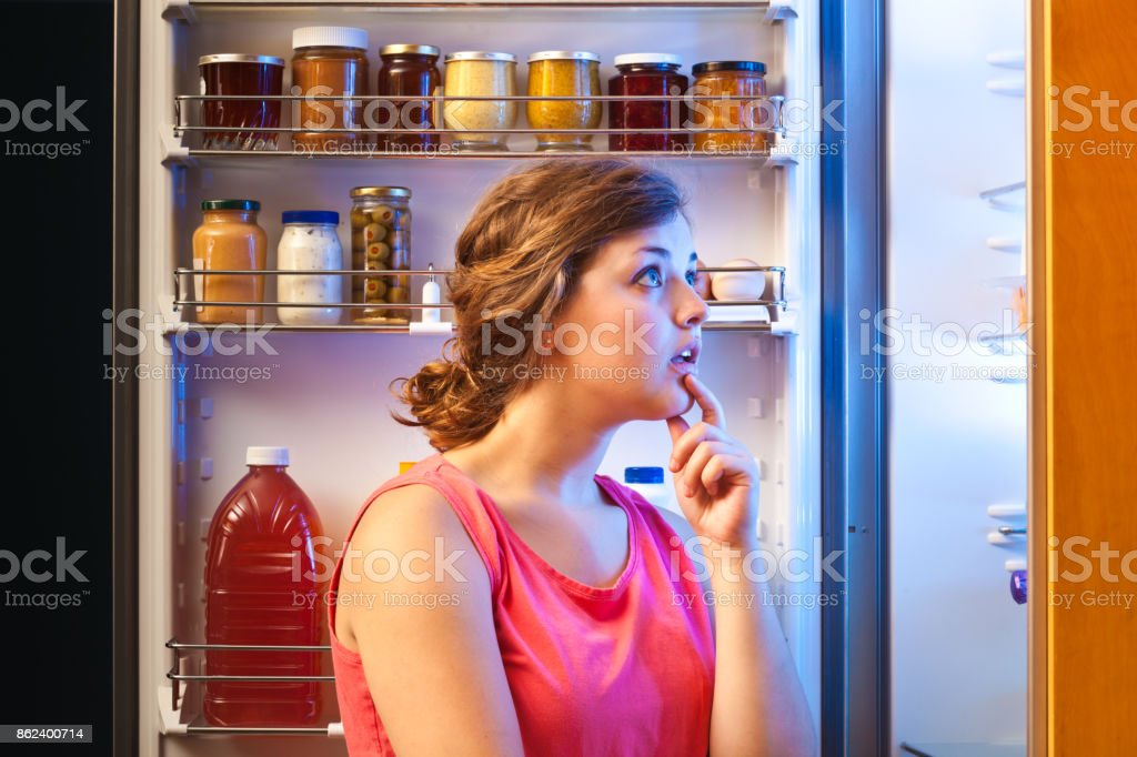 Perplex Woman Making Decision on Healthy Eating in Front of Refrigerator stock photo