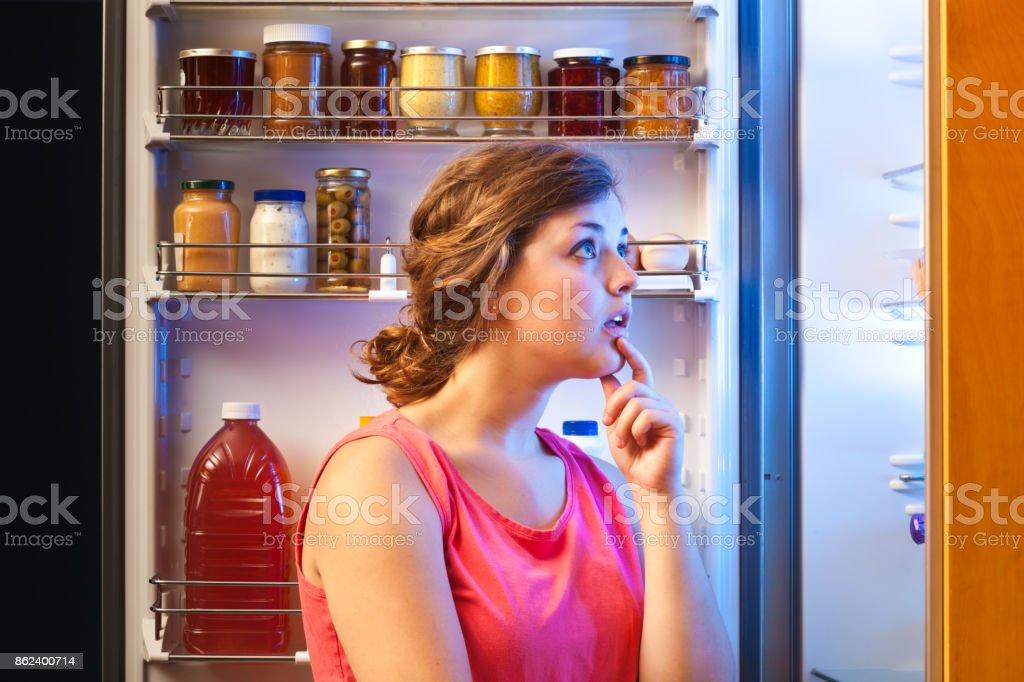 Verwirren Sie Frau, die Entscheidung über gesunde Ernährung vor Kühlschrank – Foto