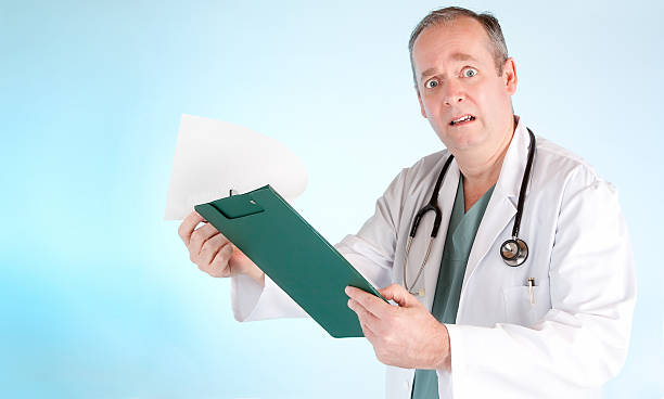 Perplexed Doctor Reading Out Disappointing Medical Test Result stock photo
